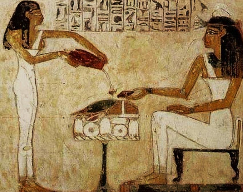 Donne dell'Antico Egitto che sorseggiano la birra.
